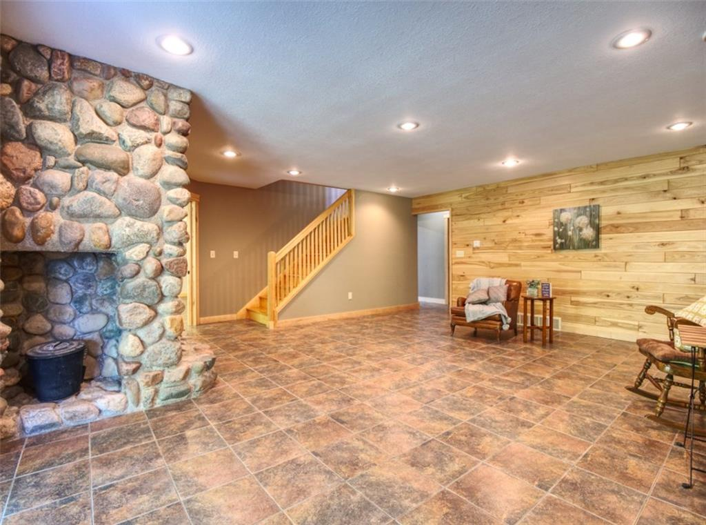 Lower level family room with 2nd field stone fireplace. This room also has a walk out slider door. - 15899 156th Street Bloomer
