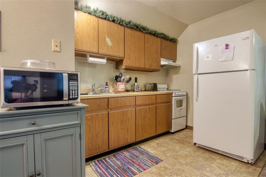 Kitchen. Full sized refrigerator and efficiency stove. Tenants personal property not included (microwave and cabinet) - 10411 State Hwy 27  Hayward